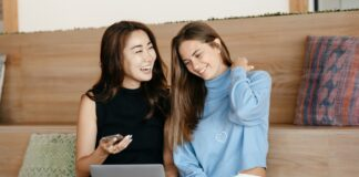 To kvinder griner med computer